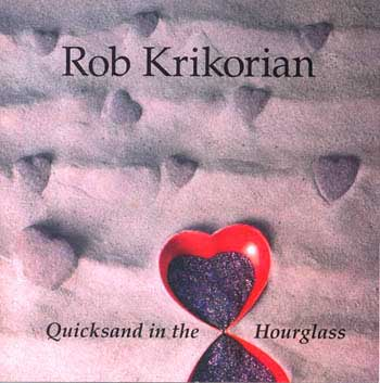 Quicksand in the Hourglass - CD front cover. Photo of an art object.  Two hearts, with points touching, form an hourglass which is lying on some sand.  The sand has several furrows, suggesting ocean waves.  In the background, numerous small hearts sink into the sand.